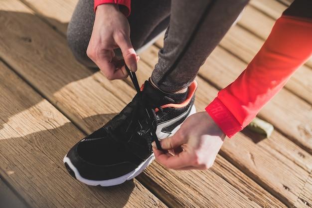 Крупным планом женщина, увязывая ее шнурки на деревянный пол