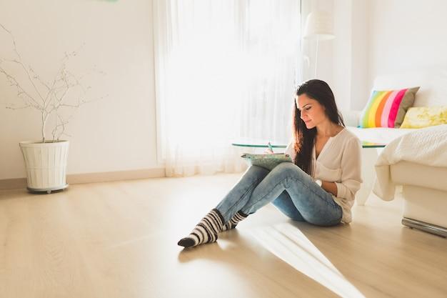 床と書き込みに座っている若い女性