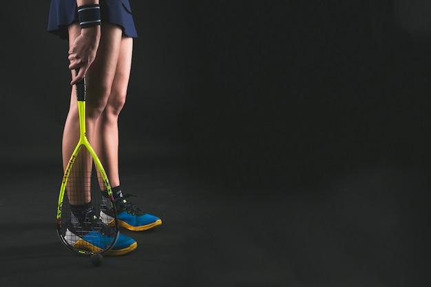 Игрок держит ракетку рядом с ее ноги