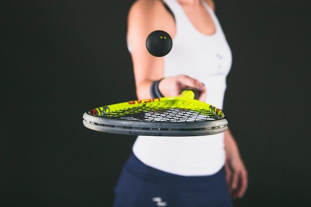 Крупным планом девушка играет с ракеткой и мячом