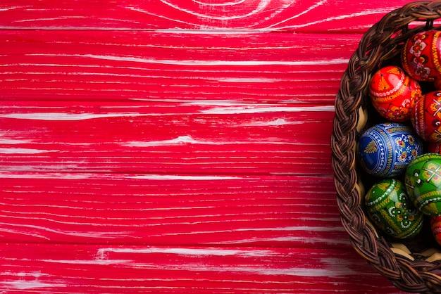 イースターの日のためのバスケットと卵と赤い木製の背景