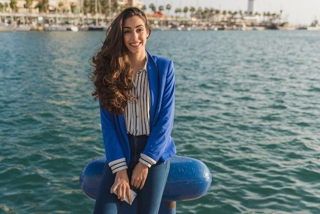 海の背景を持つ笑顔の女性
