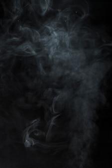 黒の背景にぼやけた煙