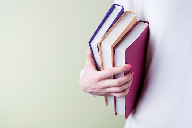 色違いでいくつかの本をつかむ手