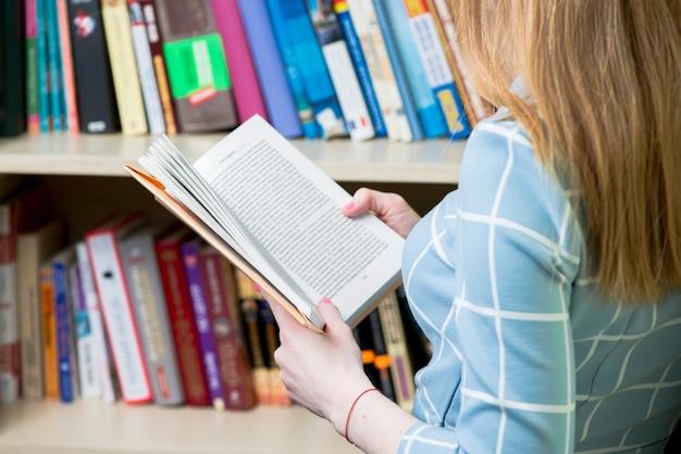 Крупный план девушки читает книгу в библиотеке