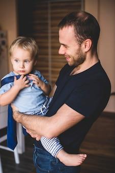 彼の父親のネクタイで遊んでいる少年