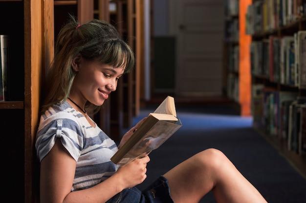 本棚に傾いている笑顔の女の子