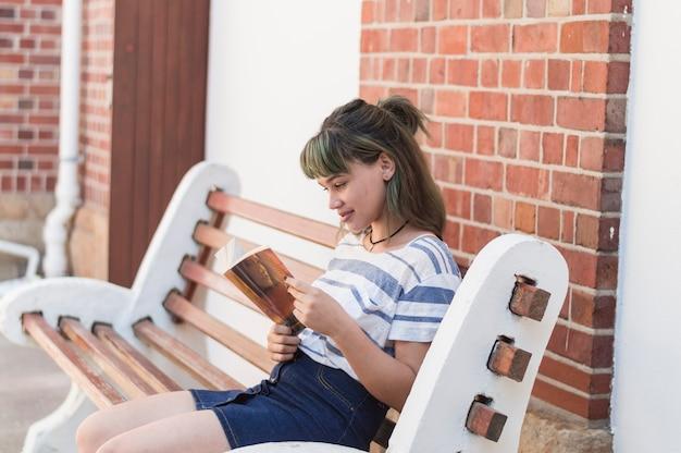 ベンチに座っている読書少女
