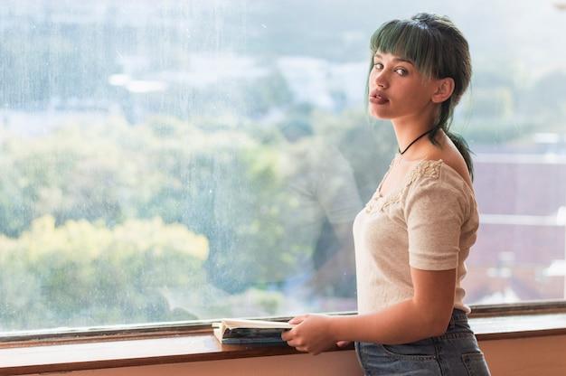 窓の前で本を持つ少女