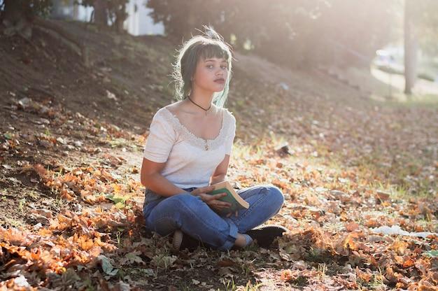 手で本を持つ丘の上に座る少女