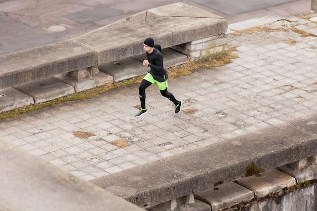 雨の多い都市で走っている男