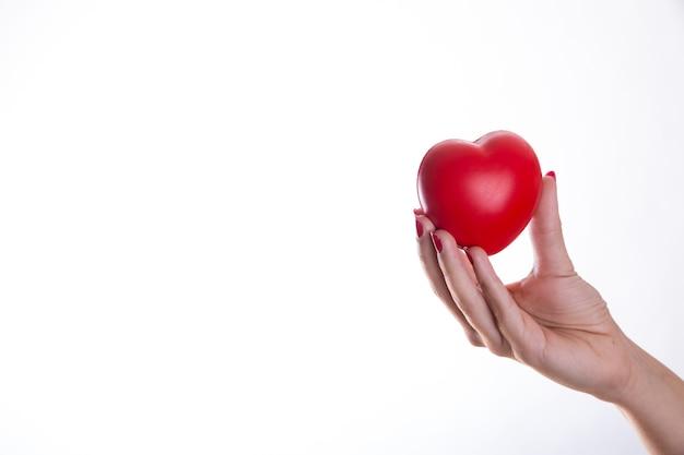 Рука с красным пластиковым сердцем