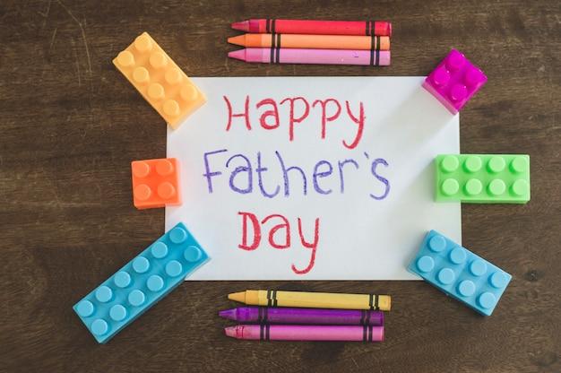 День отца, пишущий с карандашами и игрушечными кирпичами