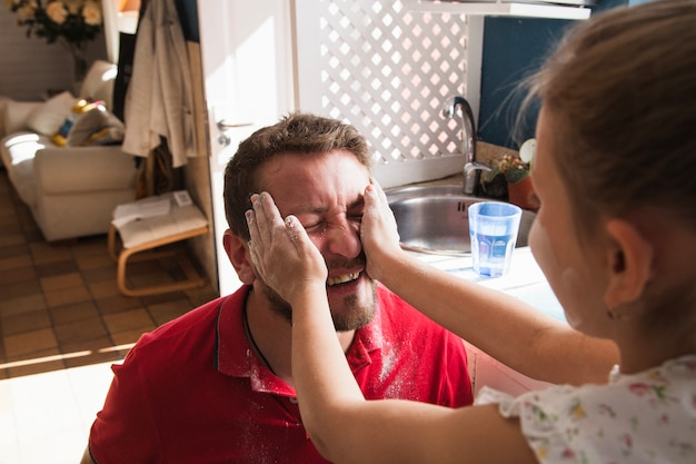 彼女の父親の顔を小麦粉で覆う女の子