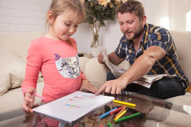 娘の絵を指している若い父親