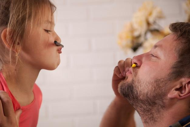 Отец и дочь играют с цветными карандашами