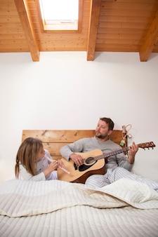 Отец и дочь с музыкальными инструментами в постели