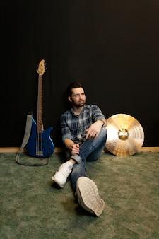 壁に腰掛けて座るギタリスト