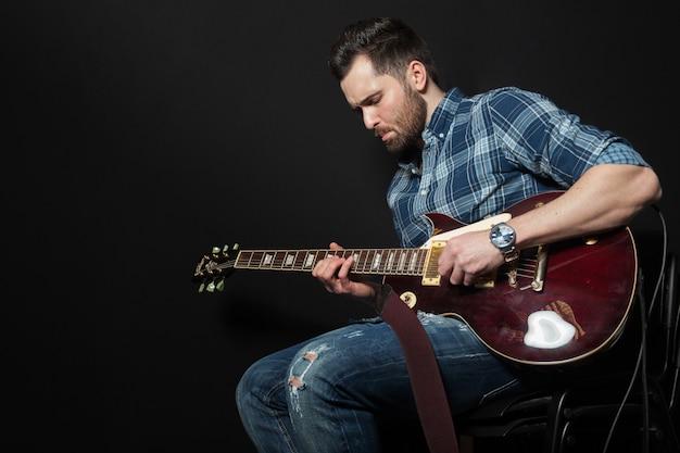 座っているギタープレーヤー