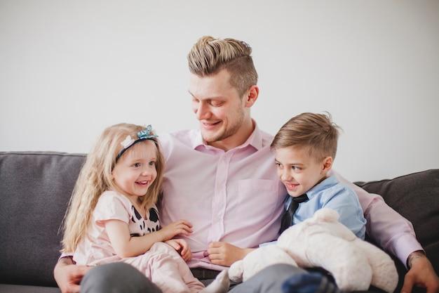 Молодой отец сидит с детьми