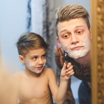 剃るために父親を助ける子供