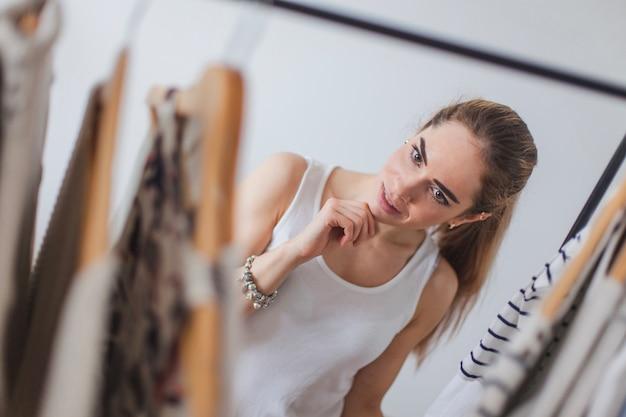 Женщина, выбирающая одежду в гардеробе