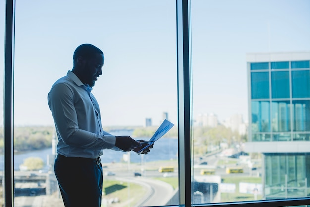 ビジネスマン、窓の前に、文書