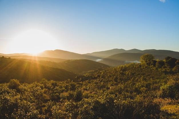 Восход солнца над холмистым ландшафтом