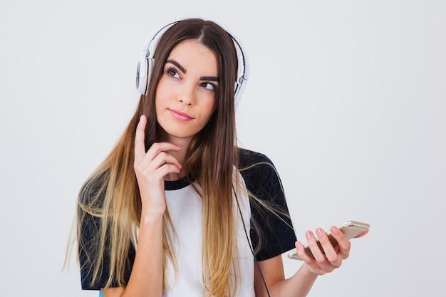 Молодая девушка, имеющая идею во время прослушивания музыки