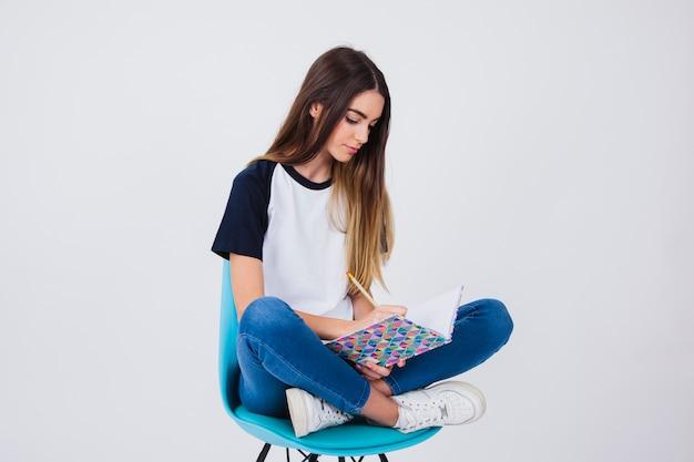 Симпатичная девушка сидит и учится