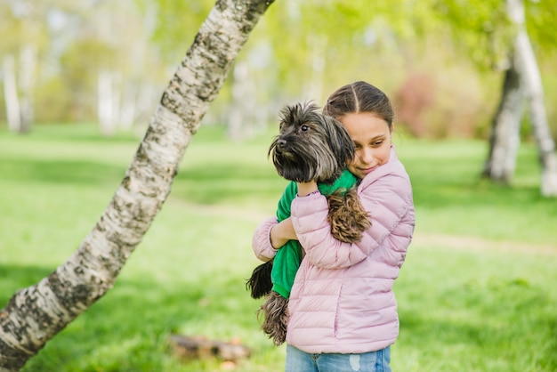 Нежная девушка обнимает свою собаку