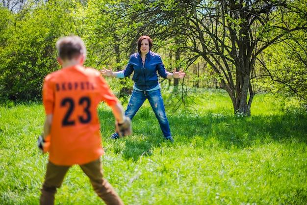 アクティブな母親は彼女の息子とサッカーをする
