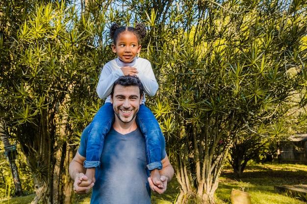 肩に女の子を運んでいる父