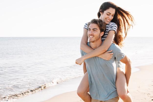 ビーチで若いガールフレンドを運ぶボーイフレンド