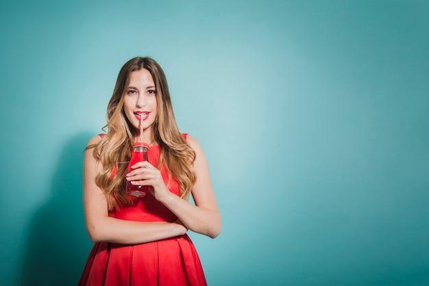赤いジュースでポーズをとっているブロンドの女の子