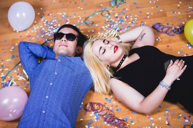 パーティーの後、床に眠っているカップル