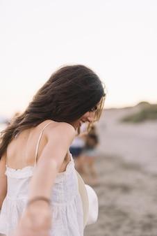 ビーチで誰かを引っ張っている少女