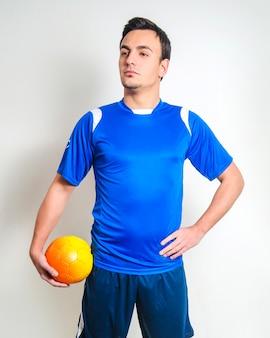 ボールでポーズをとるサッカー選手