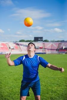 頭を使ってジャグリングするサッカー選手
