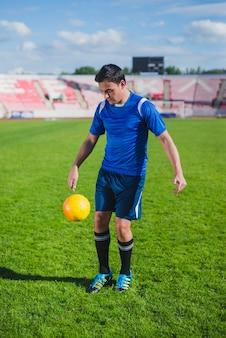 スタジアムでボールをジャグリングしているサッカー選手