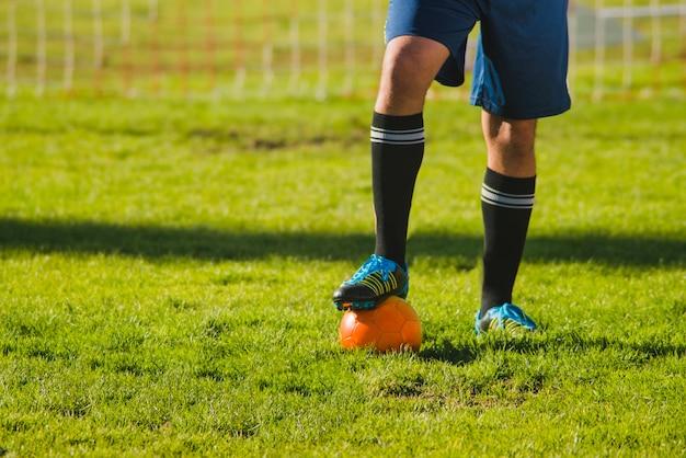 サッカー選手がボールに彼の足を置きます