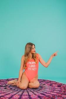彼女の左を指している水着の女の子