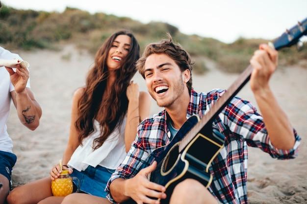 ビーチでギターを歌っている友達