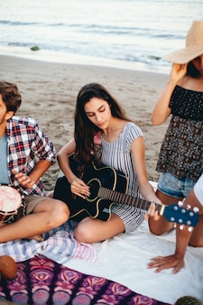 ビーチでギターを持つ女性