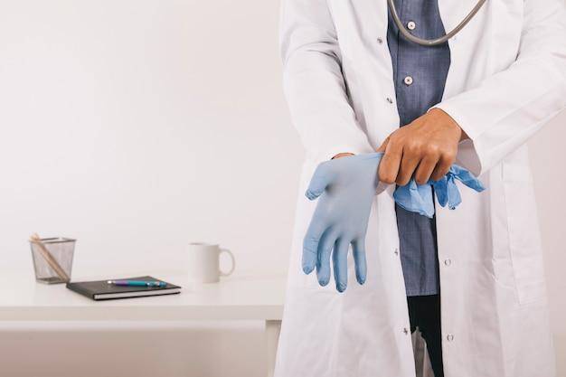Профессиональный врач в перчатках в своем кабинете