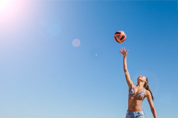 Девушка ударяет по волейболу в солнечный день