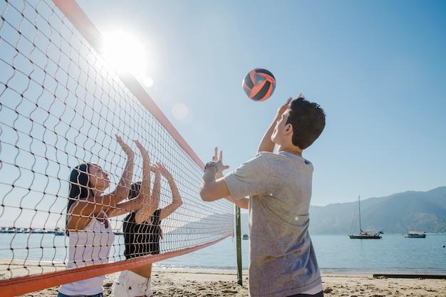 若い男たちがビーチでヴォリーを演奏する