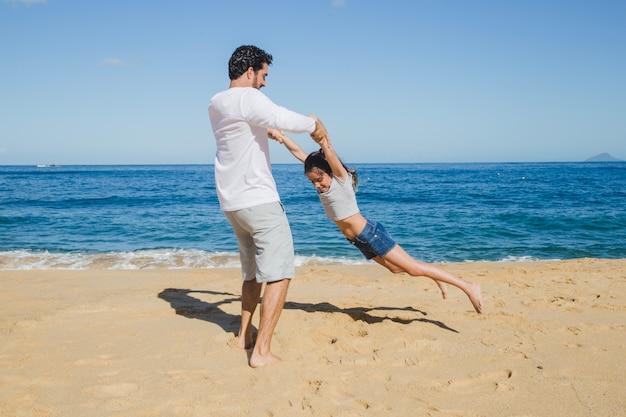 父と娘がビーチで遊ぶ
