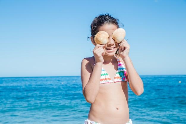 Маленькая девочка, играющая с раковинами