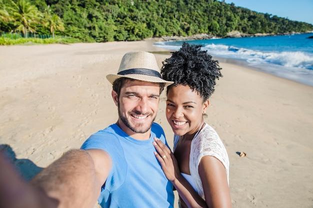ビーチでセルフをする笑顔のカップル